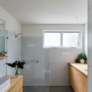 Photo of a small beach style bathroom in Gold Coast - Tweed with white tile, gray tile, subway tile, a vessel sink, wood benchtops, grey floor, flat-panel cabinets, medium wood cabinets, a curbless shower, beige walls, an open shower and brown benchtops.