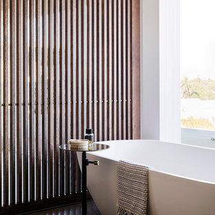 Inredning av ett modernt badrum, med ett fristående badkar, vita väggar och brunt golv