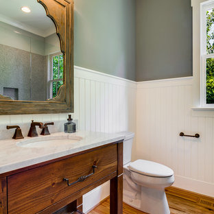 Example of a cottage medium tone wood floor bathroom design in Charlotte with an undermount sink, furniture-like cabinets, medium tone wood cabinets, green walls and a two-piece toilet