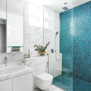シンガポールのコンテンポラリースタイルのおしゃれな浴室 (フラットパネル扉のキャビネット、白いキャビネット、段差なし、壁掛け式トイレ、青いタイル、白いタイル、モザイクタイル、大理石の床、ベッセル式洗面器) の写真