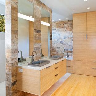Пример оригинального дизайна: главная ванная комната среднего размера в стиле модернизм с настольной раковиной, плоскими фасадами, светлыми деревянными фасадами, разноцветной плиткой, каменной плиткой, серыми стенами и полом из бамбука