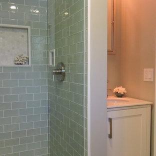 Foto di una piccola stanza da bagno con doccia costiera con lavabo sottopiano, consolle stile comò, ante bianche, top in marmo, doccia alcova, piastrelle bianche, piastrelle di vetro, pareti beige e pavimento in pietra calcarea