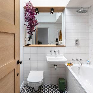 Idee per una piccola stanza da bagno con doccia design con vasca ad alcova, vasca/doccia, WC sospeso, piastrelle bianche, pareti bianche, lavabo sospeso, pavimento multicolore e doccia aperta