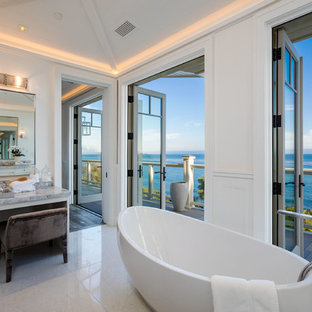 Example of a beach style white floor freestanding bathtub design in Los Angeles with recessed-panel cabinets, white cabinets, white walls and gray countertops