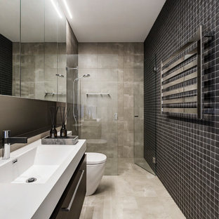 Inspiration for a contemporary 3/4 bathroom in Melbourne with flat-panel cabinets, black cabinets, an alcove shower, beige tile, black tile, grey walls, an integrated sink, beige floor, a hinged shower door and white benchtops.