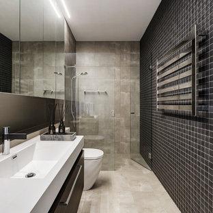 Modernes Duschbad mit flächenbündigen Schrankfronten, schwarzen Schränken, Duschnische, beigefarbenen Fliesen, schwarzen Fliesen, grauer Wandfarbe, integriertem Waschbecken, beigem Boden, Falttür-Duschabtrennung und weißer Waschtischplatte in Melbourne