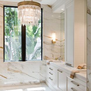 マイアミの広いビーチスタイルのおしゃれなマスターバスルーム (落し込みパネル扉のキャビネット、白いキャビネット、置き型浴槽、コーナー設置型シャワー、マルチカラーのタイル、石スラブタイル、マルチカラーの壁、セラミックタイルの床、アンダーカウンター洗面器、大理石の洗面台、白い床、オープンシャワー、白い洗面カウンター、洗面台2つ、造り付け洗面台、折り上げ天井) の写真
