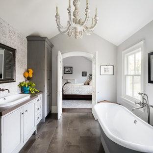 Aménagement d'une salle de bain campagne avec un placard à porte shaker, des portes de placard blanches, une baignoire indépendante, un carrelage blanc, un mur gris, un lavabo posé, un sol gris, un plan de toilette marron, meuble simple vasque, meuble-lavabo encastré et un plafond voûté.