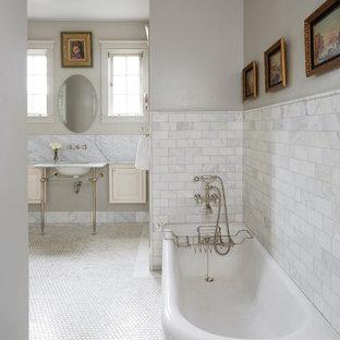 Esempio di una stanza da bagno classica con ante con riquadro incassato, ante beige, vasca ad angolo, pareti grigie, pavimento con piastrelle a mosaico e lavabo a colonna