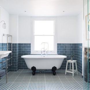 Photo of a traditional ensuite bathroom in London with open cabinets, a claw-foot bath, blue tiles, metro tiles, white walls and a console sink.