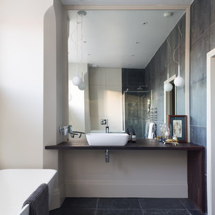 This is an example of a scandinavian bathroom in London with a freestanding bath, white walls, a vessel sink and wooden worktops.