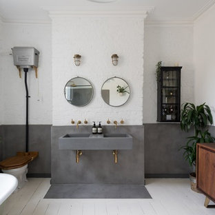 Design ideas for a large contemporary ensuite bathroom in London with flat-panel cabinets, medium wood cabinets, a freestanding bath, white walls, painted wood flooring, a wall-mounted sink, concrete worktops, white floors and grey worktops.