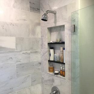 ニューヨークの小さいコンテンポラリースタイルのおしゃれな浴室 (シェーカースタイル扉のキャビネット、黒いキャビネット、ドロップイン型浴槽、シャワー付き浴槽、一体型トイレ、グレーのタイル、大理石タイル、グレーの壁、セラミックタイルの床、一体型シンク、珪岩の洗面台、マルチカラーの床、開き戸のシャワー) の写真