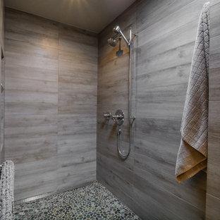 Diseño de cuarto de baño principal, moderno, de tamaño medio, con armarios con paneles lisos, puertas de armario de madera oscura, ducha abierta, baldosas y/o azulejos grises, baldosas y/o azulejos de porcelana, paredes grises, suelo de baldosas tipo guijarro, encimera de cuarzo compacto y ducha abierta