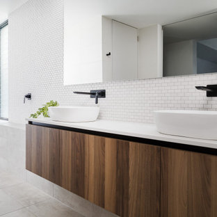 Design ideas for a modern bathroom in Perth with flat-panel cabinets, dark wood cabinets, white tile, mosaic tile, a vessel sink, grey floor and white benchtops.