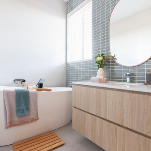 Photo of a mid-sized contemporary master bathroom in Melbourne with light wood cabinets, a freestanding tub, ceramic tile, ceramic floors, an undermount sink, engineered quartz benchtops, white benchtops, flat-panel cabinets, gray tile and grey floor.