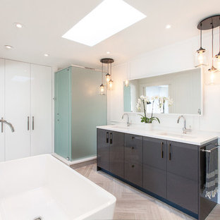 Example of a large trendy master light wood floor and brown floor bathroom design in Ottawa with an undermount sink, flat-panel cabinets, gray cabinets, solid surface countertops, white walls and a hinged shower door