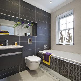 Foto på ett funkis badrum, med ett integrerad handfat, släta luckor, grå skåp, ett platsbyggt badkar, en vägghängd toalettstol, grå kakel och porslinskakel