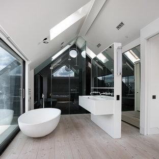 Foto de cuarto de baño actual, de tamaño medio, con lavabo de seno grande, puertas de armario blancas, bañera exenta, ducha empotrada, paredes blancas y suelo de madera clara