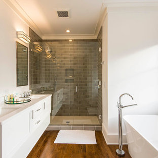 Inspiration for a mid-sized transitional master gray tile and porcelain tile medium tone wood floor bathroom remodel in Charleston with shaker cabinets, white cabinets, white walls, an undermount sink, engineered quartz countertops, a hinged shower door and white countertops