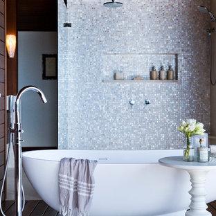 Immagine di una stanza da bagno tradizionale con vasca freestanding, vasca/doccia e piastrelle a mosaico