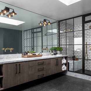 Wet room - large industrial master porcelain tile and white tile ceramic floor and black floor wet room idea with black walls, marble countertops, a hinged shower door, gray countertops, flat-panel cabinets, dark wood cabinets and an undermount sink