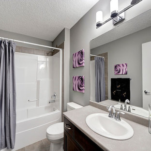 This is an example of a small classic family bathroom in Edmonton with a submerged sink, flat-panel cabinets, dark wood cabinets, laminate worktops, an alcove bath, an alcove shower, a one-piece toilet, brown tiles, ceramic tiles, grey walls and ceramic flooring.
