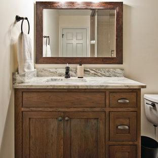 Imagen de cuarto de baño con ducha, campestre, de tamaño medio, con armarios con rebordes decorativos, puertas de armario marrones, sanitario de dos piezas, baldosas y/o azulejos blancos, paredes beige, suelo de linóleo, lavabo bajoencimera, encimera de cuarcita y suelo negro
