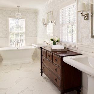 Idee per una stanza da bagno classica con lavabo a colonna, ante con bugna sagomata, ante in legno bruno, vasca freestanding e pareti bianche