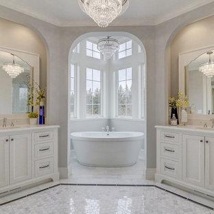 ミネアポリスの大きいトラディショナルスタイルのおしゃれなマスターバスルーム (白いキャビネット、置き型浴槽、グレーの壁、セラミックタイルの床、アンダーカウンター洗面器、珪岩の洗面台、シェーカースタイル扉のキャビネット、マルチカラーの床) の写真