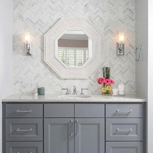 オースティンの小さいトランジショナルスタイルのおしゃれなバスルーム (浴槽なし) (シェーカースタイル扉のキャビネット、グレーのキャビネット、アルコーブ型浴槽、シャワー付き浴槽、一体型トイレ、グレーのタイル、石タイル、グレーの壁、大理石の床、アンダーカウンター洗面器、クオーツストーンの洗面台、白い床、白い洗面カウンター、開き戸のシャワー) の写真