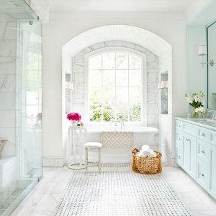 Exempel på ett stort klassiskt en-suite badrum, med ett fristående badkar, blå skåp, luckor med infälld panel, en dusch i en alkov, grå kakel, vit kakel, vita väggar, marmorgolv, ett undermonterad handfat, marmorbänkskiva och marmorkakel