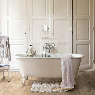 Exempel på ett mellanstort rustikt en-suite badrum, med beiget golv, ett badkar med tassar, beige väggar och laminatgolv