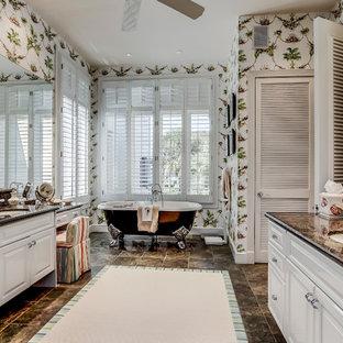 Réalisation d'une salle de bain principale tradition de taille moyenne avec un placard avec porte à panneau surélevé, des portes de placard blanches, un plan de toilette en granite, une baignoire sur pieds, un mur multicolore et un lavabo encastré.