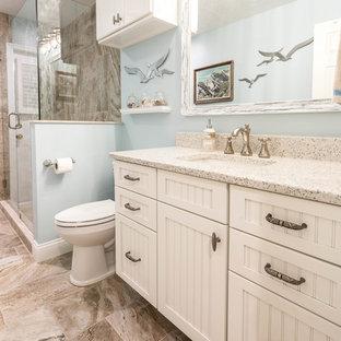Пример оригинального дизайна: большая ванная комната в морском стиле с фасадами с декоративным кантом, белыми фасадами, угловым душем, бежевой плиткой, керамогранитной плиткой, синими стенами, полом из керамогранита, душевой кабиной, врезной раковиной, столешницей из переработанного стекла, бежевым полом и душем с распашными дверями