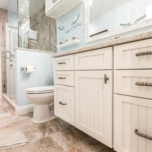 Стильный дизайн: большая ванная комната в морском стиле с фасадами с декоративным кантом, белыми фасадами, угловым душем, бежевой плиткой, керамогранитной плиткой, синими стенами, полом из керамогранита, душевой кабиной, врезной раковиной, столешницей из переработанного стекла, бежевым полом и душем с распашными дверями - последний тренд