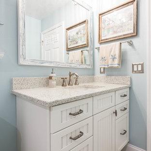 Imagen de cuarto de baño con ducha, costero, grande, con armarios con rebordes decorativos, puertas de armario blancas, ducha esquinera, baldosas y/o azulejos beige, baldosas y/o azulejos de porcelana, paredes azules, suelo de baldosas de porcelana, lavabo bajoencimera, encimera de vidrio reciclado, suelo beige y ducha con puerta con bisagras
