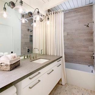 Bild på ett mellanstort maritimt badrum, med släta luckor, vita skåp, ett badkar i en alkov, en dusch/badkar-kombination, vita väggar, kalkstensgolv, ett undermonterad handfat, brun kakel och bänkskiva i betong