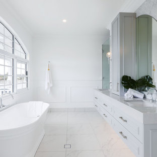Beach style bathroom in Gold Coast - Tweed with raised-panel cabinets, grey cabinets, a freestanding tub, gray tile, white walls, an undermount sink, white floor, grey benchtops and a double vanity.