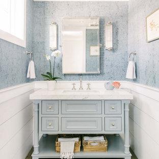 ロサンゼルスのビーチスタイルのおしゃれな浴室 (落し込みパネル扉のキャビネット、グレーのキャビネット、グレーの壁、無垢フローリング、アンダーカウンター洗面器、茶色い床、白い洗面カウンター、洗面台1つ、独立型洗面台、羽目板の壁、壁紙) の写真