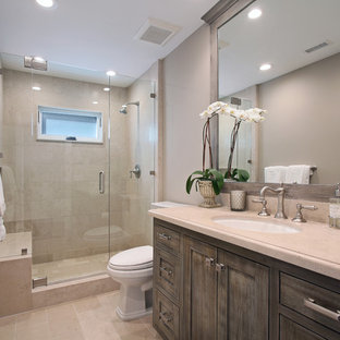 Design ideas for a mid-sized traditional kids bathroom in Orange County with dark wood cabinets, beige tile, marble floors, recessed-panel cabinets, an alcove shower, a two-piece toilet, porcelain tile, grey walls, an undermount sink, limestone benchtops, beige floor, a hinged shower door and beige benchtops.