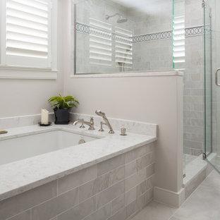 Foto di una grande stanza da bagno padronale tradizionale con vasca sottopiano, doccia ad angolo, piastrelle grigie, pareti grigie, porta doccia a battente, piastrelle di marmo, pavimento in marmo, top in quarzo composito e pavimento grigio