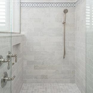 На фото: большая главная ванная комната в классическом стиле с фасадами с утопленной филенкой, серыми фасадами, полновстраиваемой ванной, угловым душем, раздельным унитазом, бежевыми стенами, полом из керамогранита, врезной раковиной, столешницей из кварцита, серым полом, душем с распашными дверями и желтой столешницей с