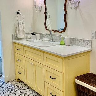 Ispirazione per una stanza da bagno country di medie dimensioni con ante in stile shaker, ante gialle, pareti bianche, pavimento in gres porcellanato, lavabo da incasso, top in quarzo composito, pavimento multicolore e top bianco