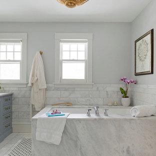 Modelo de cuarto de baño principal, ecléctico, con armarios con paneles lisos, puertas de armario azules, bañera encastrada sin remate, ducha empotrada, baldosas y/o azulejos grises, baldosas y/o azulejos de mármol, paredes grises, suelo con mosaicos de baldosas, lavabo bajoencimera, encimera de mármol, suelo gris, ducha con puerta con bisagras y encimeras blancas