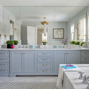 Ejemplo de cuarto de baño principal, bohemio, con armarios con paneles lisos, puertas de armario azules, bañera encastrada sin remate, ducha empotrada, baldosas y/o azulejos grises, baldosas y/o azulejos de mármol, paredes grises, suelo con mosaicos de baldosas, lavabo bajoencimera, encimera de mármol, suelo gris, ducha con puerta con bisagras y encimeras blancas