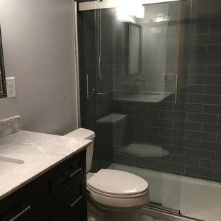 他の地域の小さいモダンスタイルのおしゃれなマスターバスルーム (レイズドパネル扉のキャビネット、グレーのキャビネット、段差なし、一体型トイレ、グレーのタイル、グレーの壁、クッションフロア、アンダーカウンター洗面器、大理石の洗面台、グレーの床、引戸のシャワー、白い洗面カウンター) の写真
