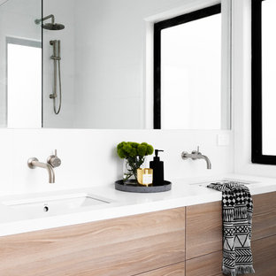 This is an example of a contemporary bathroom in Melbourne with flat-panel cabinets, light wood cabinets, white walls, an undermount sink, black floor and white benchtops.