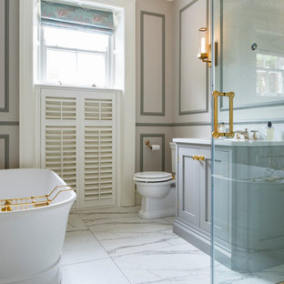 This is an example of a classic ensuite bathroom in London with shaker cabinets, grey cabinets, a freestanding bath, white floors, white worktops and multi-coloured walls.