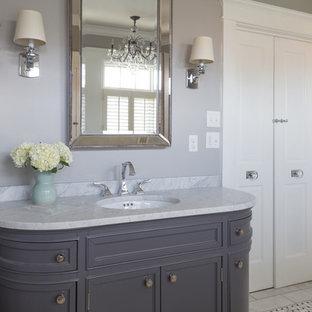 Imagen de cuarto de baño principal, clásico, grande, con lavabo bajoencimera, armarios tipo mueble, puertas de armario grises, encimera de ónix, bañera exenta, ducha esquinera, sanitario de dos piezas, baldosas y/o azulejos blancas y negros, baldosas y/o azulejos en mosaico, paredes grises y suelo de mármol